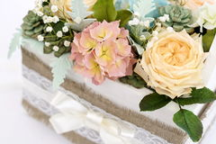 A bouquet of sugar flowers in a wooden white box. Royalty Free Stock Image