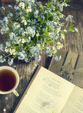 Bouquet of summer blue flowers, cup of tea and vintage books. On wooden table royalty free stock photo