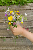 Bouquet of summer wildflowers in hand. On a wooden surface background stock photo