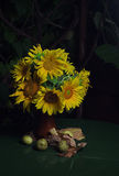 Bouquet of sunflowers on a green table. Still life with flowers and pears on a dark background Royalty Free Stock Photography