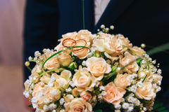 Bouquet tea rose with wedding rings. The groom holds a bouquet. Wedding day Royalty Free Stock Images
