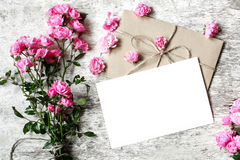 Bouquet of tender pink roses with a blank greeting card and envelope Stock Image