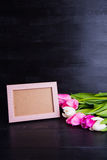 Bouquet of tender pink tulips and empty photo frame on black woo Stock Image
