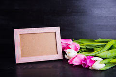 Bouquet of tender pink tulips and empty photo frame on black woo Stock Photography