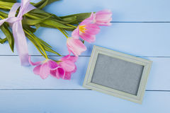 Bouquet of tender pink tulips with empty photo frame on blue woo Stock Photos
