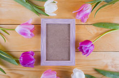Bouquet of tender pink tulips with empty photo frame on light wo Royalty Free Stock Photo