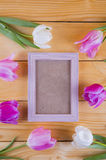 Bouquet of tender pink tulips with empty photo frame on light wooden background. Stock Image