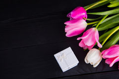 Bouquet of tender pink tulips with gift box on black wooden back Stock Images