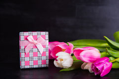 Bouquet of tender pink tulips with gift box on black wooden back Royalty Free Stock Images