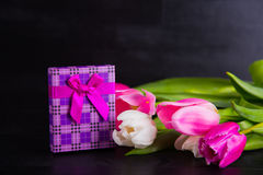 Bouquet of tender pink tulips with gift box on black wooden back Stock Photography