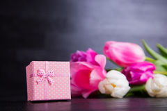 Bouquet of tender pink tulips with gift box on black wooden back Royalty Free Stock Photos