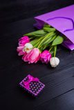 Bouquet of tender pink tulips with gift box on black wooden back Royalty Free Stock Photo