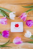 Bouquet of tender pink tulips with greeting card on light wooden Stock Photo