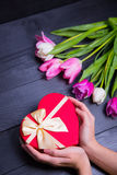 Bouquet of tender pink tulips and hands holding gift box on blac. Beautiful bouquet of tender pink and white tulips with female hands holding gift box in shape Royalty Free Stock Photos