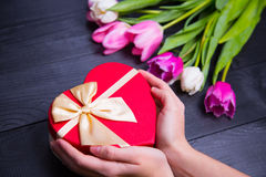 Bouquet of tender pink tulips and hands holding gift box on blac Royalty Free Stock Images