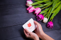 Bouquet of tender pink tulips and hands holding greeting card on Stock Photo