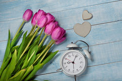 Bouquet of Tulips with alarm clock and a wooden heart Stock Images
