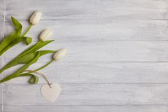 Bouquet of tulips with blank tag in a heart shape stock photo