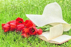 Bouquet of tulips, a book, a hat on the grass Royalty Free Stock Photography