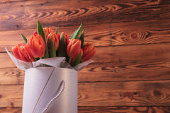Bouquet of tulips in a box on old wood background Royalty Free Stock Photography