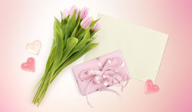 Bouquet of tulips, card, hearts and box gift on pink Royalty Free Stock Image