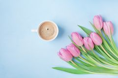Bouquet of tulips and coffee cup on blue pastel table top view. Beautiful spring breakfast on Mothers or Womans day. Flat lay. royalty free stock images
