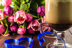 Bouquet tulips and cup coffee cup,heart on wooden table Royalty Free Stock Photos
