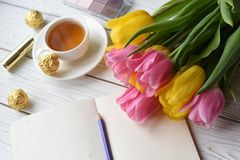 A bouquet of tulips, a cup of tea, some sweets, a note book, some jewellery, eye. A photo representing a spring concept for women - a bouquet of tulips, a cup of Royalty Free Stock Photography