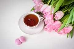 Bouquet of tulips and cup of tea on white background. Holiday card. royalty free stock images