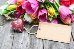 Bouquet of tulips with an empty tag and red heart Royalty Free Stock Photo