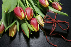 Bouquet of tulips and gift box on black background Royalty Free Stock Images