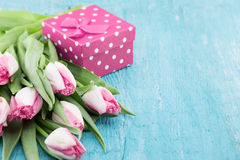 Bouquet of Tulips and gift box on turquoise rustic wooden backgr Stock Photos