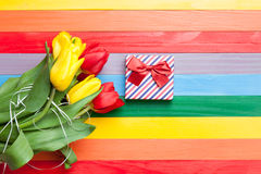 Bouquet of tulips and gift. On color wooden background Royalty Free Stock Image