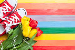 Bouquet of tulips and gumshoes. On color wooden background Royalty Free Stock Images