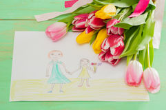 Bouquet of tulips and kids picture with mother and daughter on t Royalty Free Stock Image