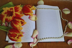 Bouquet of tulips with a notebook royalty free stock image