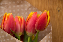Bouquet of tulips. In paper with polka dots on the wooden board Royalty Free Stock Photos
