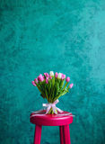 Bouquet of tulips on pink chair. Bouquet of pink and white tulips with pink ribbon on the green painted wall background standing on pink chair. Empty space for royalty free stock photo