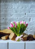 Bouquet of tulips with pink ribbon on the gray brick wall backgr. Bouquet of tulips with pink ribbon on the gray brick wall and firewood background stock images