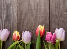 Bouquet of tulips of spring flowers on old wooden board on holid. Bouquet of tulips of spring flowers on old wooden board on a holiday of Easter Stock Image
