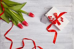 Bouquet of tulips with white gift box decorated with red ribbon stock photo
