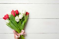 Bouquet of tulips on white wooden table, copy space for text. Invitation or congratulation banner mockup for spring holidays, Inte royalty free stock photo