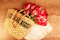 Bouquet of tulips in a wicker bag2. Red-white rippled tulips in a wicker basket on a sacking background Stock Photo