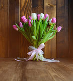 Bouquet with tulips on wooden background. Beautiful bouquet with pink and white tulips standing on wooden background stock photo
