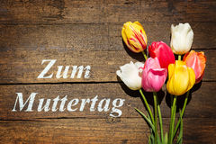 Bouquet of Tulips on wooden background and german words mother´ Royalty Free Stock Photography