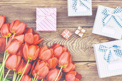Bouquet of Tulips on Wooden Table with Presents. Beautiful Bouquet of Orange Tulips on Wooden Table with Presents in Assorted Sizes, Captured in High Angle View Stock Photo