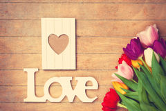 Bouquet of tulips and word Love near photo frame Royalty Free Stock Photos