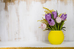 Bouquet of tulips in a yellow vase on a wooden background. Stock Photo