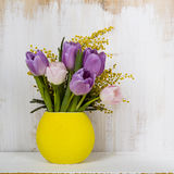 Bouquet of tulips in a yellow vase on a wooden background. Royalty Free Stock Image