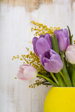 Bouquet of tulips in a yellow vase on a wooden background. Stock Photos